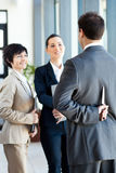Dangerous businessman. Hiding knife behind his back while handshaking with businesswoman Royalty Free Stock Photo