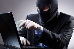 Dangerous businessman uses a laptop. With gloves Royalty Free Stock Photo