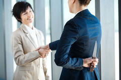 Dangerous businesswoman. Holding knife behind her back while handshake Royalty Free Stock Photos