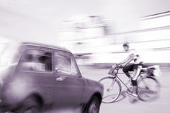 Dangerous city traffic situation with a cyclist and a car Royalty Free Stock Photo