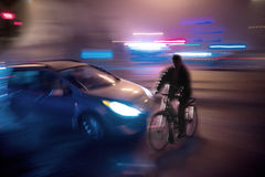 Dangerous city traffic situation with cyclist and car. In the city at night in motion blur Royalty Free Stock Photography