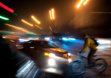 Dangerous city traffic situation. With cyclist and car in the city at night in motion blur Royalty Free Stock Photo