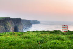 Dangerous cliff edge. Cliffs of Moher at sunset, Co. Clare, Ireland Royalty Free Stock Photo