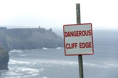 Dangerous cliff edge sign in overcast weather at Cliffs of Moher in Ireland. Danger sign warning. stock photo