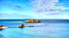 Dangerous cliff rocks rises from the sea. High Definition Photo of dangerous cliff rocks rising from a deep blue sea. Clear azure skyline lasts to the horizon Stock Photography