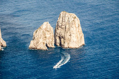 Dangerous cliff rocks rises from the sea. Two hight cliff rocks with grottos rising above a deep blue water. Small motor yacht passing it by Royalty Free Stock Images