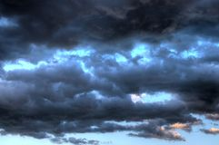 Dangerous clouds stormy heavy blue sky at dusk. Amazing stormy sky with heavy clouds emotional view with colorful spectrum Royalty Free Stock Photo