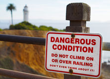 Dangerous Condition. Dangerous sign with the lighthouse far away Royalty Free Stock Image