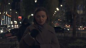 Dangerous criminal following young woman walking on night city street, bandit