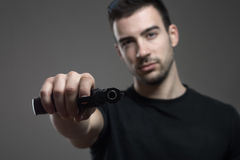 Dangerous criminal holding tilted gun threatening aiming at camera. Atmospheric contrasty portrait over gray studio background Royalty Free Stock Photos