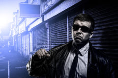Dangerous criminal man. Portrait of stylish dangerous man with weapon standing on the poor street at night/ early morning Royalty Free Stock Photography