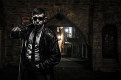 Dangerous criminal man on the street at night. Dangerous hooligan man wearing leather coat,black sunglasses, classic white shirt with black tie-neck, is standing Royalty Free Stock Photos