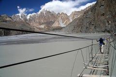 Dangerous Crossing. Girl crossing dangerous bridge over Hunza river in Karakorum in Pakistan Royalty Free Stock Image