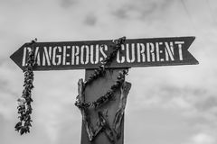 A Dangerous current sign with dried leis at Waimea Beach, in the north shore of Oahu, Hawaii. A Dangerous current sign with dried leis at Waimea Beach stock photography