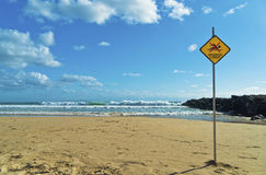 Dangerous Current Warning Sign on Beach. Dangerous current sign on beach. Diamond shaped orange or yellow sign with figure of swimmer crossed out with red. Sign Royalty Free Stock Images