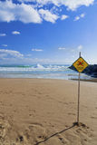 Dangerous Current Warning for Swimmers on Beach. Dangerous current sign on beach. Diamond shaped orange or yellow sign with figure of swimmer crossed out with Royalty Free Stock Photos