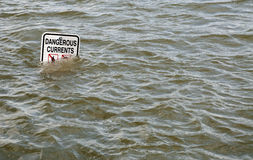 'Dangerous Currents' sign in flooded river Royalty Free Stock Image