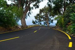 Dangerous curve 2. A dangerous curve in a winding mountain road with yellow marks stock photo