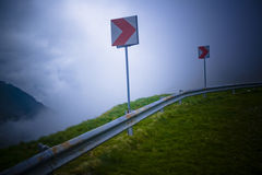 Dangerous Curve. Mountain road curb sign in a high atmosphere area stock photo