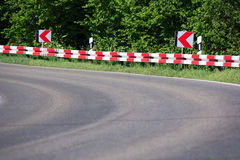 Dangerous curve. With arrow sign and striped barrier royalty free stock photo