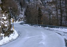 Dangerous curve of a frozen mountain road Royalty Free Stock Photos