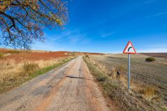 Dangerous curve sign on rural road with potholes. Dangerous curve sign on lonely bumpy rural road with potholes, with old asphalt in poor condition pavement, in royalty free stock images