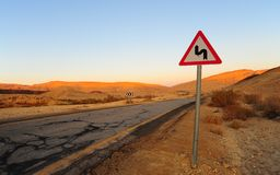 Dangerous Curves. Road Sign At The Abandoned Road. Sunset Royalty Free Stock Photo