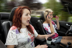 Dangerous driving. Distracted driver applying makeup and talking on phone while driving Stock Image