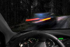 Dangerous driving. In dark wet conditions on narrow rural road Stock Image