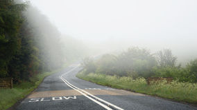 Dangerous driving on road in fog: slow mark Stock Photos