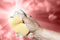Dangerous effects of cleaning products. The hand of a woman is squeezing a sponge making soap come out from it. Background is a sunny sky completely red coloured Stock Photography