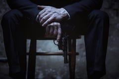 Dangerous elegant villain holing a gun royalty free stock photography