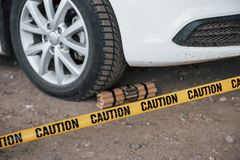 Dangerous explosive near the wheel of modern white car. Yellow caution tape in front