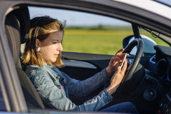 Dangerous female driver. Reading a text message on her smartphone and taking her attention off the road, profile view Stock Photography