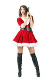 Dangerous femme fatale dressed as Santa Claus woman holding pistol Stock Photos