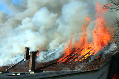 Dangerous fire. Roof of an old building caught on fire Stock Image