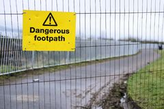 Dangerous footpath walkway sidewalk warning sign for pedestrians walkers people public danger do not walk yellow signage on constr royalty free stock image