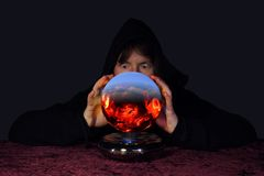 Dangerous future. A gypsy fortune teller seeing terrible things in a crystal ball Stock Image