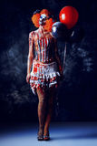 Dangerous games. Evil redhead clown stained in blood holding balloons. Female zombie clown. Halloween. Horror Stock Photos
