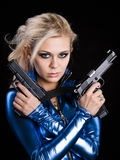 Dangerous girl. Martial young lady with two guns royalty free stock photos