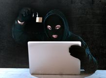 Dangerous hacker man with computer and lock hacking system in cyber crime concept. Hacker man in black hood and mask with computer laptop holding lock in royalty free stock photo