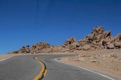 Dangerous hairpin curve in two lane highway with rocks piled on horizon above the tree line on Pikes Peak in Colorado.  stock image