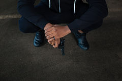 Dangerous hardened criminal squatting. Waiting for somebody. Dangerous hardened male criminal squatting and holding a handgun while waiting for somebody Stock Photography