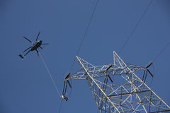Dangerous High Voltage Power Line Work From A Helicopter. A high-voltage power line repairmen is suspended from a helicopter as he is lifted into position Stock Photography