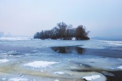 Dangerous hobby-winter fishing. Dnipro River was covered with first thin ice but the lovers of winter fishing are already fishing. Morning view of Obolon Stock Images