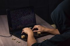 Hooded hacker using laptop to steal bitcoin royalty free stock photos
