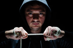 Dangerous hooded male. Hooded Male with an intimidating expression, against Dark Background Stock Images