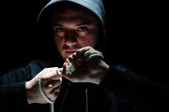 Dangerous hooded male. Hooded Male with an intimidating expression, against Dark Background Royalty Free Stock Image