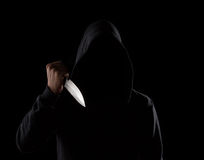 Dangerous hooded man holding knife stock photography