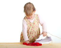 Dangerous housework - little girl ironing Stock Images